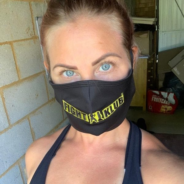 A blonde girl with blue eyes wearing a black branded Fight Klub facemask